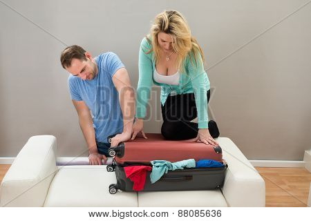 Couple Trying To Close Luggage