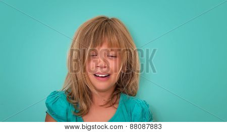 Crying child on turquoise background. Emotions.