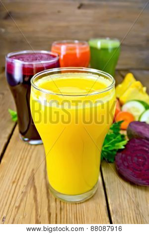 Juice pumpkin and vegetable in glassful on board
