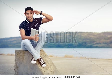 Young Man with Sunglasses and Tablet by the Water