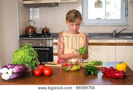 Little girl cooking at home kitchen. Healthy Food - Vegetable Salad. Diet. Dieting Concept. Healthy
