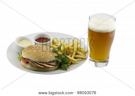 Glass of beer, a burger, french fries and sauce