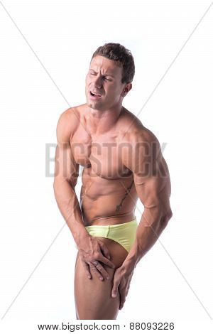 Muscular handsome man holding his thigh and leg in pain