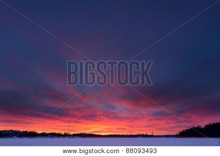 Vibrant and colorful sunset over frozen lake during Winter in Stockholm, Sweden