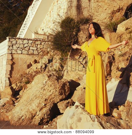 young woman with long yellow dress posing outdoor
