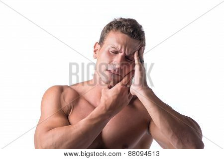 Muscular handsome man holding his head with for headache, isolated