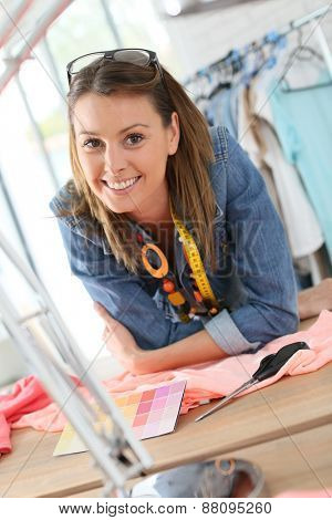 Portrait of cheerful dressmaker in designing studio