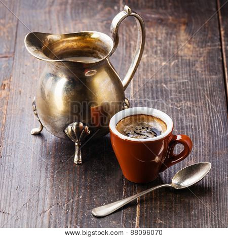 Coffee Cup And Silver Creamer On Wooden Background