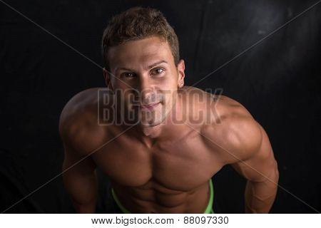 Handsome shirtless bodybuilder shot from above, standing