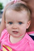 pic of teething baby  - A cute baby girl sits outside in the summertime with her mom - JPG
