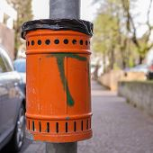 stock photo of polution  - Trash orange metal for the collection of waste of the road - JPG