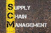 foto of supply chain  - Acronym SCM- Supply Chain Management. Business Conceptual image with yellow paint line on the road over asphalt stone background. - JPG