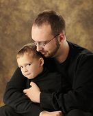picture of snuggle  - Close up image of a father snuggling with his young son who is grinning at the viewer from the corner of his eye - JPG
