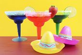image of party hats  - Happy Cinco de Mayo colorful party theme with bright color margarita drinks on red wood table and yellow background - JPG