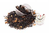 picture of black tea  - Aromatic black dry tea with petals and a tea strainer on white reflective background - JPG