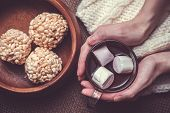 image of crispy rice  - Woman holding cup of cocoa with marshmallows on woollens and rice crispy balls in wooden bowl - JPG