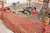 image of manhole  - Orange fence around the construction site and metal worker is in a manhole - JPG
