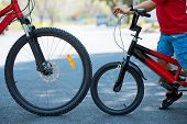 stock photo of riding-crop  - Side view of wheels of father and son bicycles - JPG