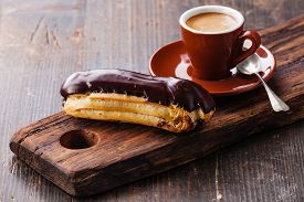 stock photo of eclairs  - Chocolate eclair and coffee cup on dark wooden background - JPG