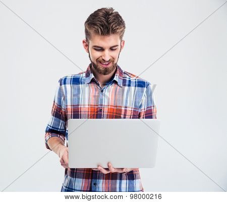 Happy young man using laptop isolated on a white background