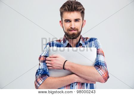 Portrait of a unshaved handsome man holding laptop isolated on a white background