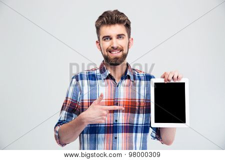 Portrait of a smiling man pointing finger on blank tablet computer screen isolated on a white background. Looking at camera