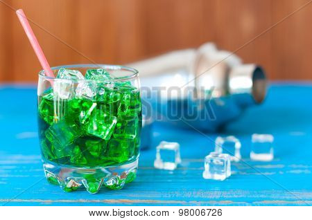 close up green alcohol cocktail with cubes of ice and shaker on bluewooden table