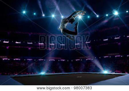 Young girl is jumping on trampoline