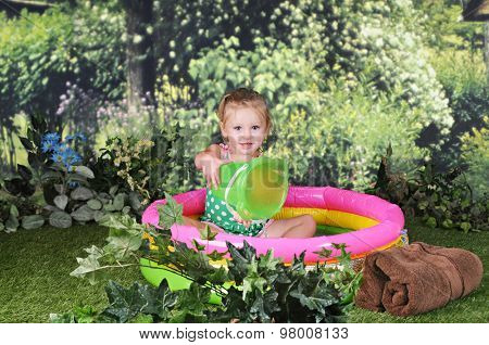 An adorable two year old outside happily playing in a small kiddie pool.