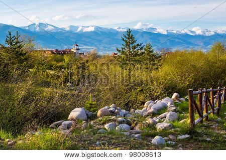 Spring Landscape With Wooden Fence, Trees, Part And Snowy Mountains