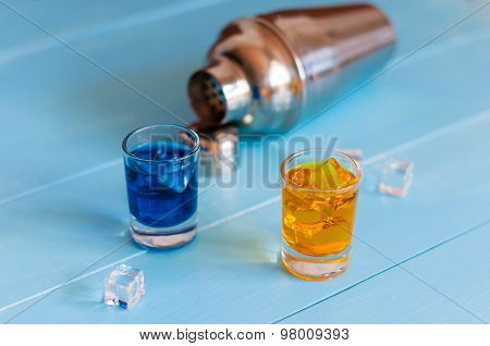 Blue and orange shots near metal sheker on wooden background