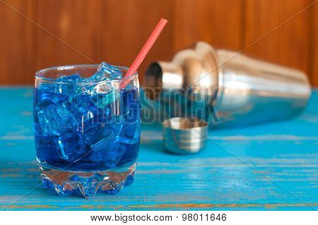 tropical blue cocktail served on a out of focus bar. With defocused metal shaker background
