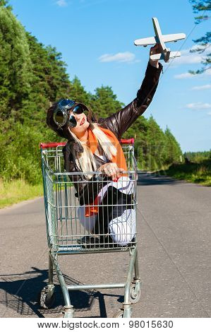 woman in aviator helmet on the trolley with toy airplane outdoors