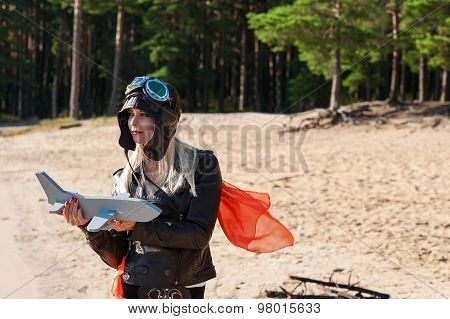 dreaming woman in aviator helmet on the on the beach with toy airplane
