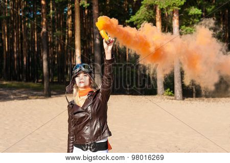 beautiful woman dressed as a pilot standing on the shore of the beach with a colored smoke bombs