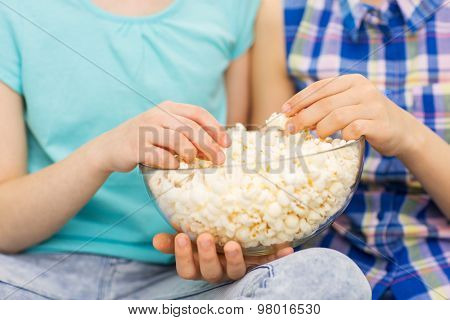 people, children, friends and junk food concept - close up of little girls eating popcorn from bowl