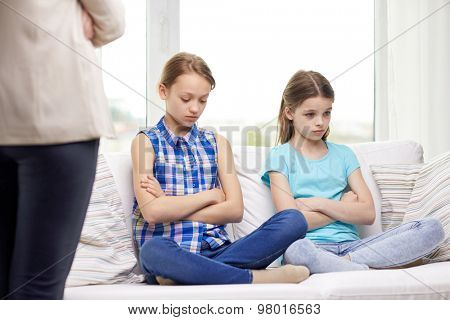 people, children, misbehavior, friends and friendship concept - upset feeling guilty or displeased little girls sitting on sofa and mother at home