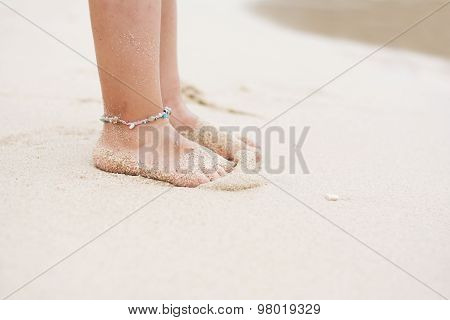 Barefoot Child With Ankle Bracelet On Beach