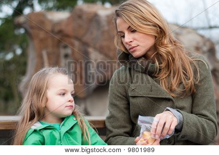 Mother And Daughter Having A Snack Outside