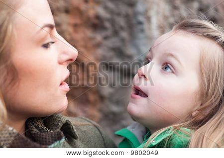Amazed Little Girl On Mother's Hands