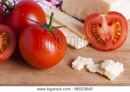 Tomatoes And Cheese On Chopping Board