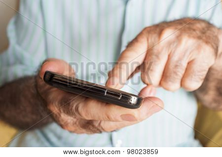 closeup of an old caucasian man sitting in an armchair uses a smartphone