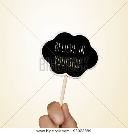 closeup of the hand of a young woman holding a chalkboard in the shape of a thought bubble with the text believe in yourself written in it