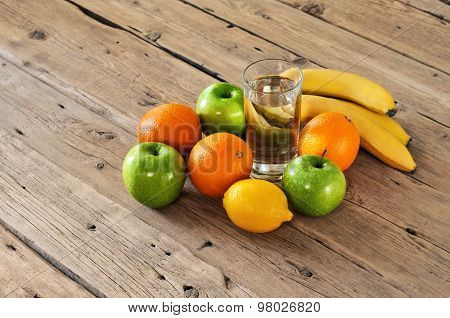 Fruit With A Glass Of Water On A Wooden Table