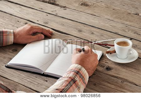 Hand Of Man Writing Something In Blank Notebook On Wooden Table