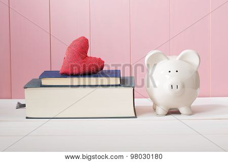 White Piggy Bank Beside Books With Red Heart Cushion