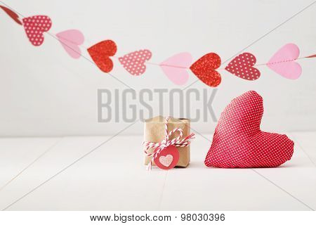 Garland Of Hearts Above Small Giftbox And Red Heart Cushion