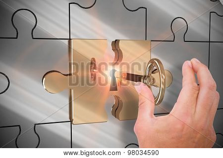 Hand presenting against key unlocking jigsaw
