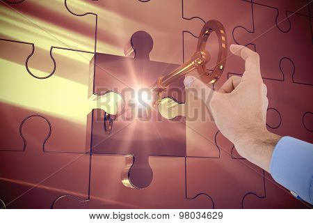 Businessman holding hand out in presentation against key unlocking jigsaw