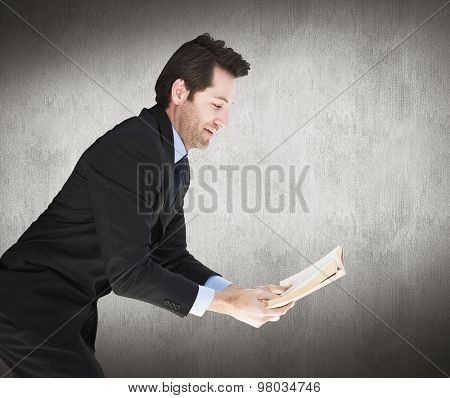 Businessman lying on the floor while reading a book against white and grey background